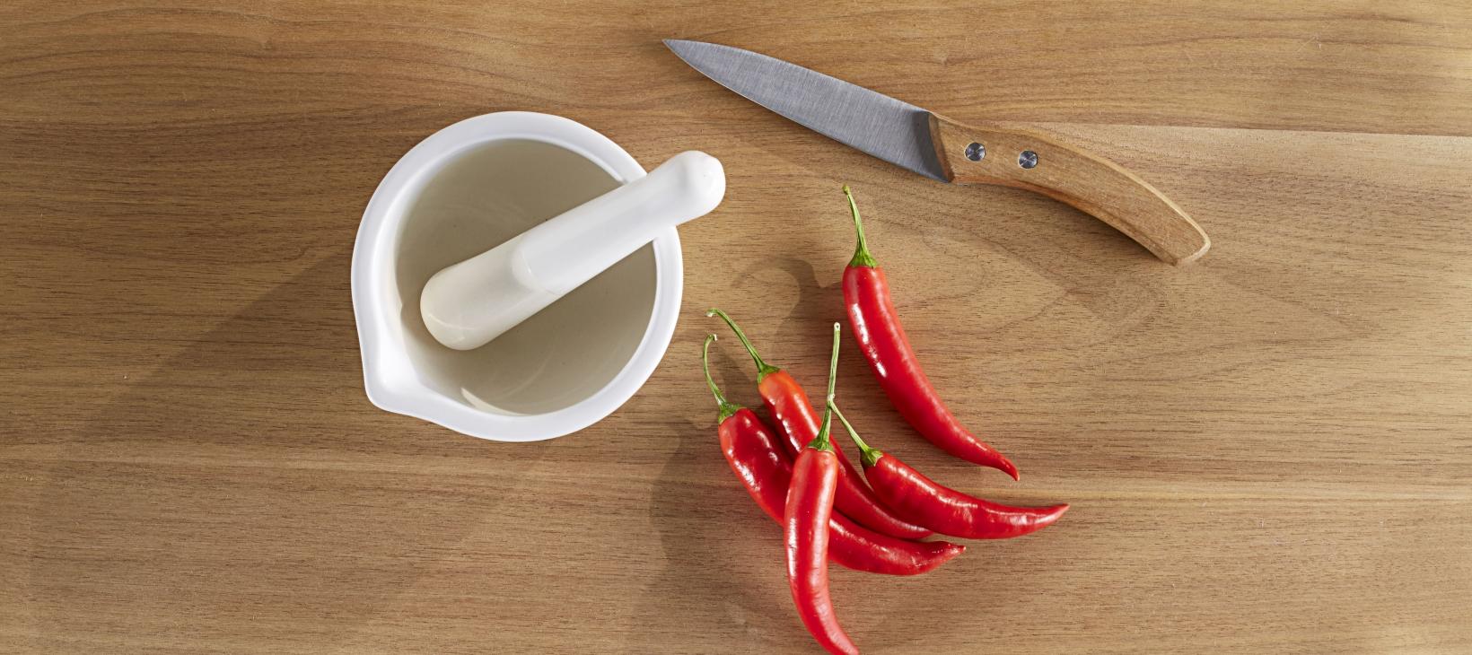 Mörser, Chilischoten und Messer
